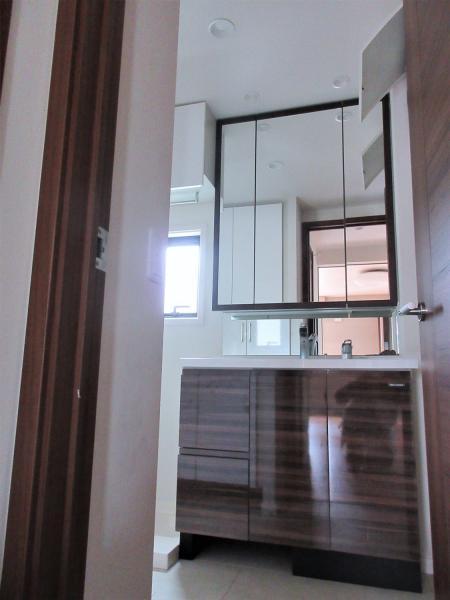 三面鏡付き独立洗面台。洗面所は窓あり。